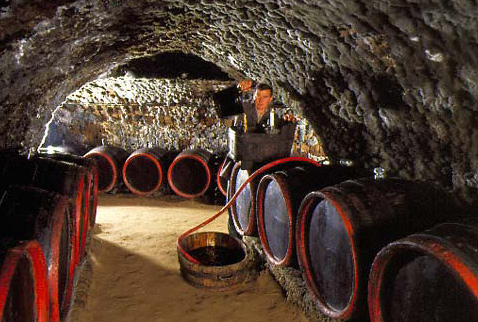 Регион виноделия Токай - Gyula Borsos racking wine in the traditional manner in the ancient, mould-covered cellars of Tokaj Kereskedцhуz, Tolcsva, Hungary. [Tokaji]